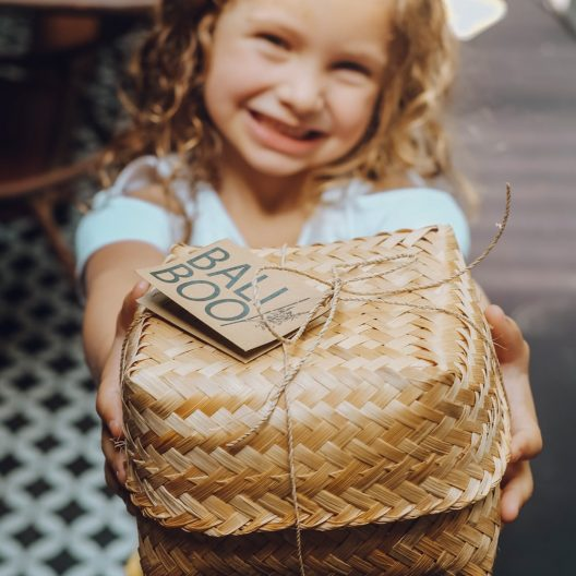 girl gifting a handwoven basket with a coconut bowl set
