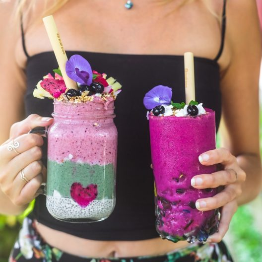 a girl holding two colorful smoothies with bamboo strawss