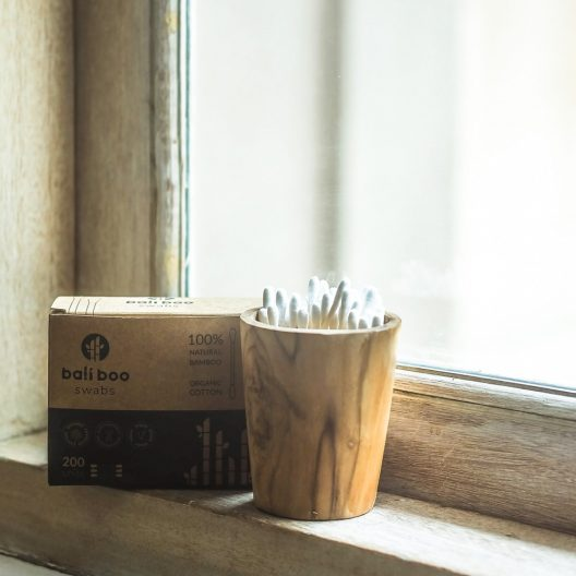 cotton swabs next to a window on a bahtroom