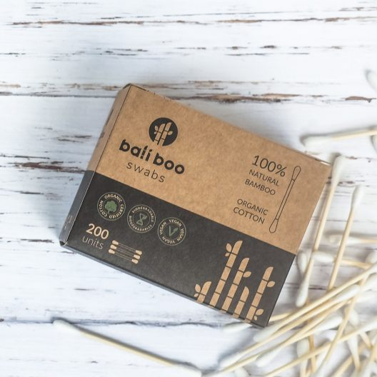 bamboo cotton swabs next to a pack of cotton swabs of Bali Boo on a table
