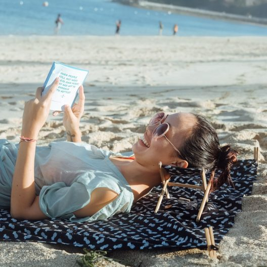 a girl reading a book using the Bali Boo Beach Headrest on the beach.